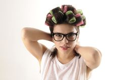 Girl arranging hair with curlers Royalty Free Stock Images