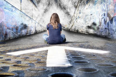 Girl and Arrow. An artistic image of a girl, in an industrial setting, sitting near an arrow and facing a grungy wall Stock Photos