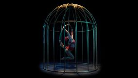 Girl art acrobatics on a spinning hoop in a cage. Black background. Girl art acrobatics in the string hangs upside down on a spinning hoop in a cage. Black stock video