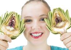 Girl with Artichoke halves. Young Girl with Artichoke halves stock photos