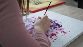 Girl artist draw abstract paintings with inscriptions. Motivational inscriptions. Coworking.