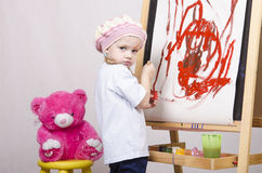 Girl, the artist draws on easel bear Stock Photography