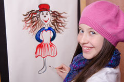 Girl artist draws a funny girl Stock Photography