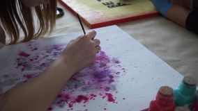 Girl artist draws letters on the color board. Craft. Art Studio. Collaboration. Master Class. Artistic education. Paint cans and brushes. Spray paint stock footage