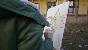 Girl artist hand painting in old city street.  stock video footage