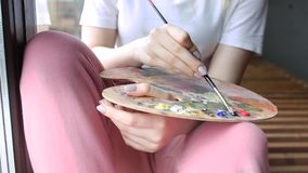 Artist hands with brush mixing colors on palette close up. Art, creativity, hobby. Girl artist hands with brush mixing colors on palette close up. Art stock video footage