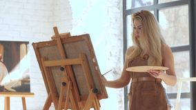 Girl artist inspired paints picture on canvas mounted on easel. In hands holds brush and palette, in background large light window and other works of master stock video footage