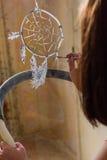 Girl artist painting on glass dream catcher. Beautiful girl artist paints on glass figure stock photo