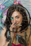 Girl artist painting on glass dream catcher. Beautiful girl artist paints on glass figure royalty free stock photography