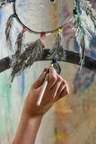 Girl artist painting on glass dream catcher. Beautiful girl artist paints on glass figure royalty free stock photos