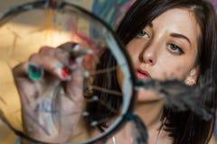 Girl artist painting on glass dream catcher. Beautiful girl artist paints on glass figure stock image