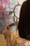 Girl artist painting on glass dream catcher. Beautiful girl artist paints on glass figure royalty free stock images