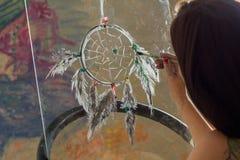 Girl artist painting on glass dream catcher. Beautiful girl artist paints on glass figure stock images