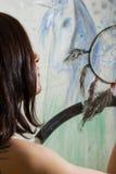 Girl artist painting on glass dream catcher. Beautiful girl artist paints on glass figure stock photography