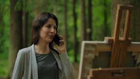 Girl artist painting a picture in the forest and talking by mobile phone. Talking with loved ones over the phone during favorite outdoor hobby. Happy stock footage