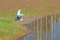 Girl artist paints an autumn landscape, in a park, next to a pond stock photo