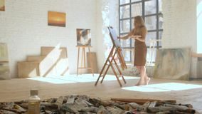 Girl artist paints on canvas on easel and holds palette in art workshop. Girl artist paints on canvas on easel and holds palette, in the foreground tubes with stock video footage