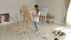 Girl artist paints on canvas painting on the easel. Pretty Girl artist paints on canvas painting on the easel. Art, creativity, hobby, job and creative stock video footage