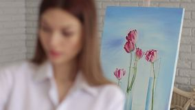 Girl artist paints on canvas painting on the easel. Pretty Girl artist paints on canvas painting on the easel. The girl draws a picture in the Studio, the focus stock video