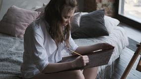 The girl artist paints a picture in the home studio. The artist is working on a painting in the morning. stock footage