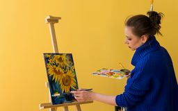 Girl artist paints sunflowers. Stock Photo