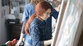 Girl artist with red hair draws paints on an easel stock video footage