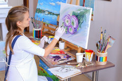 Girl artist sits with back to camera and draws oil picture with Stock Photography