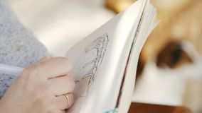 Girl artist in sunglasses draws sketches in notebook stock footage
