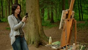 Girl artist takes a picture of her painted picture on a smartphone. Beautiful tall brunette paints a landscape in an open air in the forest and taking a photo stock footage