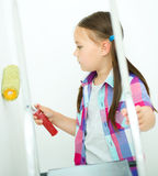 Girl as a construction worker with paint roller Stock Images