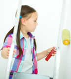 Girl as a construction worker with paint roller Royalty Free Stock Image