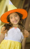 Girl as Halloween Witch. A smiling girl with brown eyes and long brown hair in pigtails, wears an orange, yellow and white witch costume, with a tall hat, for Stock Photography