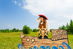 Girl as pirate holds helm and bends her arm Stock Images