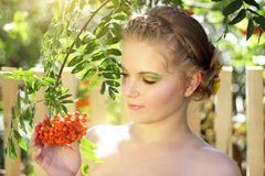 Girl with ashberries. On a light background Royalty Free Stock Image