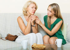 Girl asking for forgiveness from her mother. Teen girl asking for forgiveness from her mother. Focus on mature woman stock image