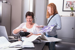 Girl is asking her mother in home office for money Stock Image