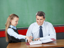 Girl Asking Question To Male Professor At Desk Royalty Free Stock Photo