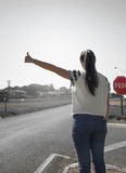 Girl asking for a ride on the roadside of a highway Royalty Free Stock Image