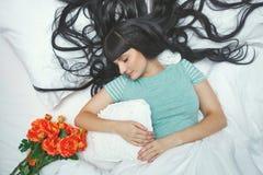 Girl asleep in bed. Flowers. Stock Image