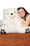 Girl asleep leaning against a teddy bear Royalty Free Stock Images