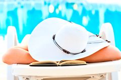 Girl asleep in a lounge chair near the pool with a book Stock Photo