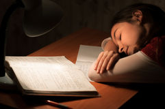 Girl asleep at a table doing homework Royalty Free Stock Photo