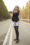 Girl assassin waiting for his victim on the road. Royalty Free Stock Photos