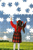 The girl assemble big puzzle Royalty Free Stock Photos