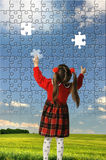 The girl assemble big puzzle Stock Image