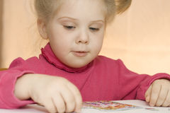 Girl assembles puzzles Royalty Free Stock Photo