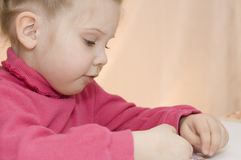 Girl assembles puzzles Stock Images