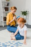 Girl assembling puzzle. While mother using smartphone Stock Photos