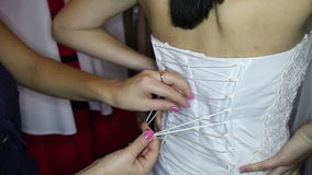 Girl assistant ties corset to bride stock video