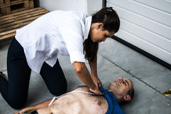 Girl assisting an unconscious man. Girl assisting an unconscious men after cardiac arrest and applying defibrillator electrodes Royalty Free Stock Photos